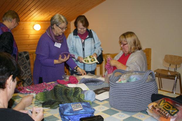 Ulpu Räty-Haliseva esittelee Pirkan Opiston lankatyökurssin töitä Marjo-Riitta Saloselle.