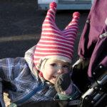 Puolitoistavuotias Elma Nieminen kurkki lapasen takaa kuin tonttu ikään.