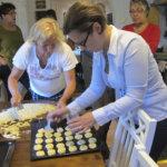 Marika Vecsei näytti suomalaisille isännille, miten leivotaan unkarilaisia perunakakkaroita. Avustajana Jutta Järvinen (oik.)  Kuva: Ritva Mäkelä