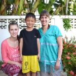 Milja Lassila kyykistyneenä Lassilan perheen thaimaalaisen kummipoika Chenropin, 7., vierellä. Mari Lassilan (oik.) paita on Chenropin äidin kutoma Karen-heimon asu.