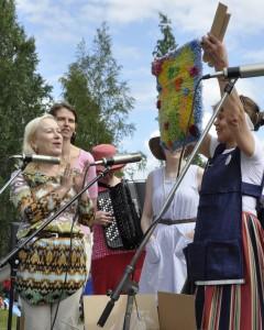 Eeva Nytorp esittelee uutta ryijyä markkinayleisölle Narvassa. Värikäs ryijy on suunniteltu lasten huoneen seinälle. Vasemmalla Tiina Nopola ja Minna Polus.
