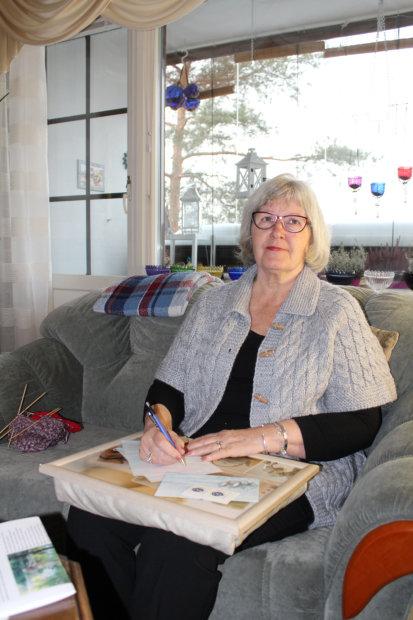 Sirpa Ahola on istahtanut lempituoliinsa kirjoittamaan kirjettö ystävälleen. Kuva: Erkki Koivisto