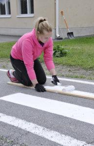Milana Hutko maalaa suojatietä Kirkonkylä koulun pihaan. Kuva: Katariina Onnela