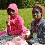 Fatou, 9, ja Sukai, 7, tulivat kesälomanviettoon mummolaan Lempäälään ja herkuttelivat Myllyrannan perhepiknikillä jäätelöillä. Kuva: Katariina Onnela