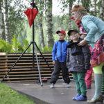 Alberttiinan johdolla Kasper, Anni ja Viljo sekä muu yleisö taikoivat Nuuskamuikkusen huuliharpun taikurin hattuun. Kuva: Katariina Onnela