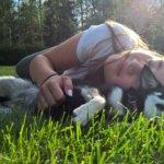 Parhaat ystävykset Christina ja Elli-koira loikoilevat nurmikolla leikistä väsyneinä. Kuva: Satu Pasanen