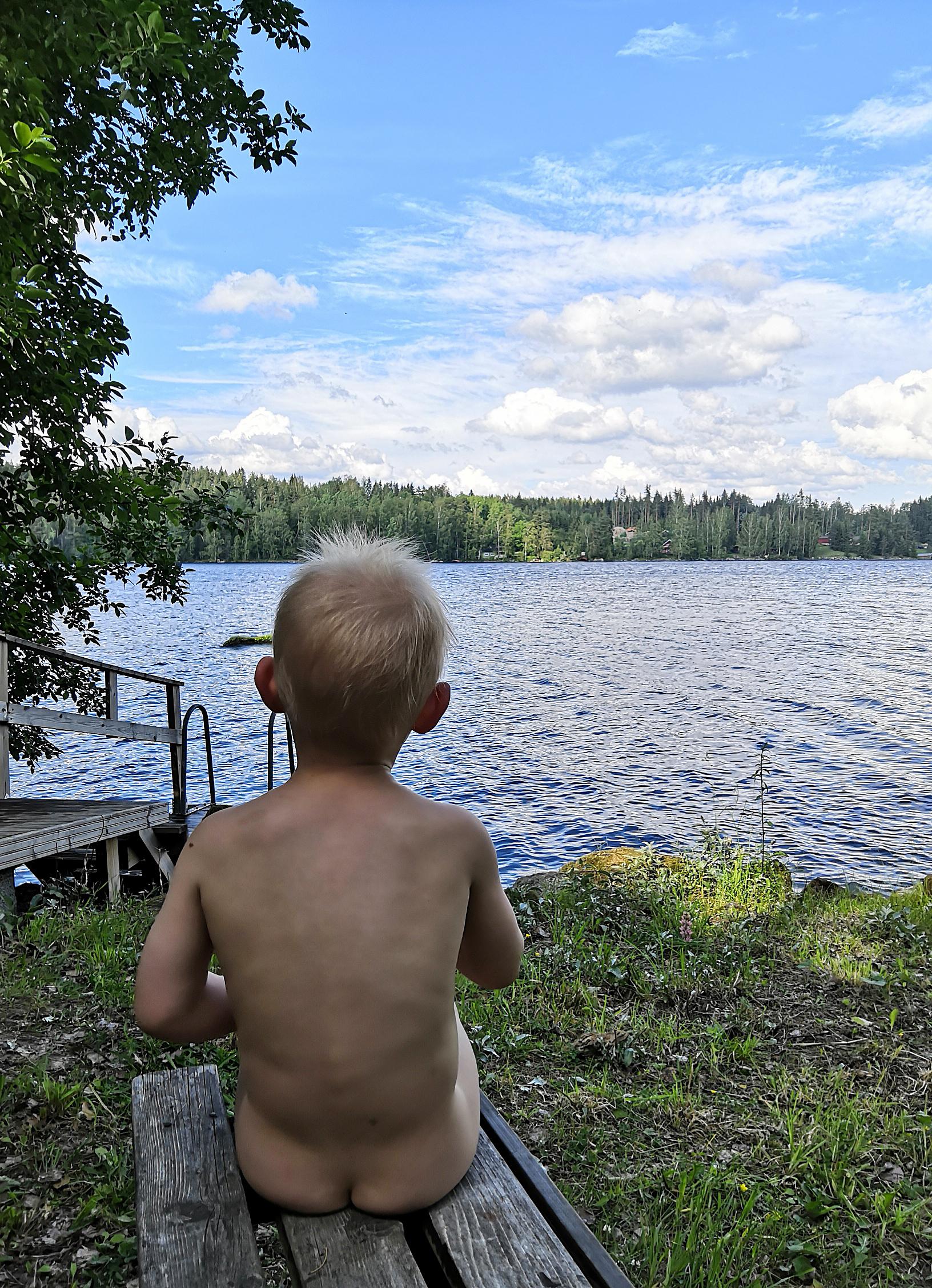 2-vuotias Vili nauttii suomalaisesta järvimaisemasta juhannussaunan jälkeen vilvotellen. Kuva: Henna Laineenoja