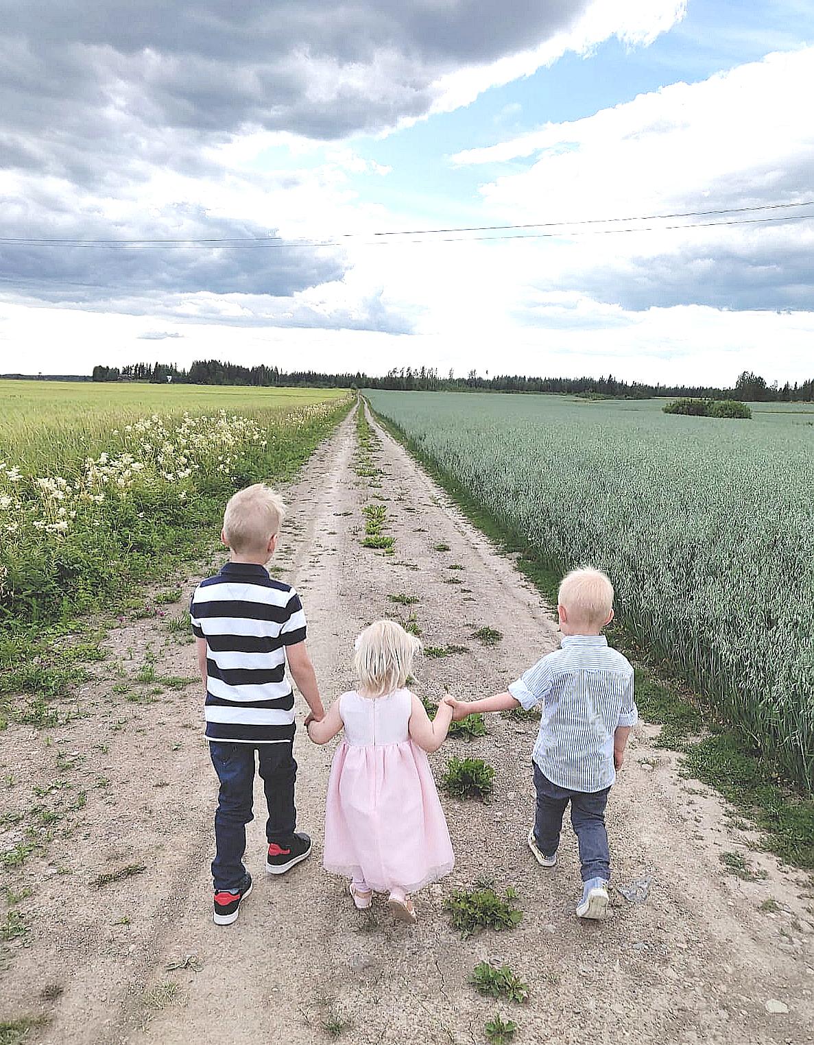 Milo ja Vili sekä keskellä Sara-serkku kävelyllä peltomaisemissa. Kuva: Henna Laineenoja